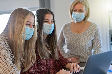 Twin sisters and their teacher wearing protective mask and working their lesson on a laptop at home during lockdown due to covid-19 Reklamní fotografie