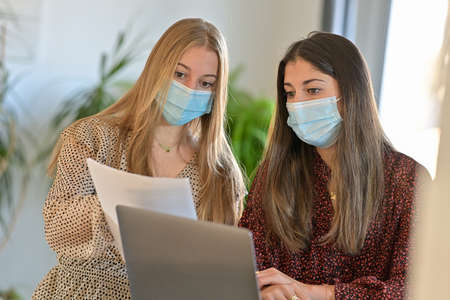 Young female friends wearing a protective mask while they are working at home and attending at a webinar on their laptop during the lockdown Reklamní fotografie