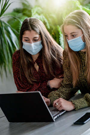 Female friends are browsing on their laptop at home or are chatting with their friends on a social network while they are wearing a protective mask due to the covid-19 Reklamní fotografie