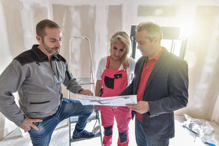 Explanations between an architect and craftmen responsible for the renovation of an apartment