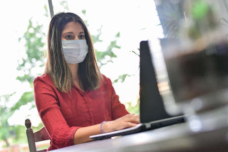 Young woman wearing a protective mask while she is working at home and attending at a meeting on her computer during the lockdown Reklamní fotografie