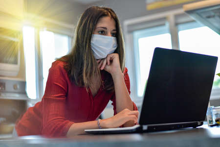 Young female worker wearing a protective mask while she is at home and attending at a meeting on her computer during the lockdown