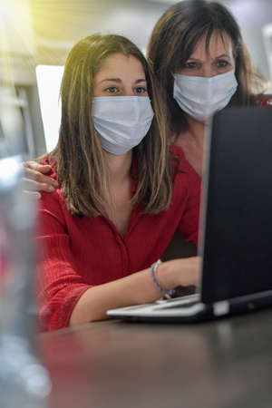 Mother and daughter wearing protective mask and browsing and shopping on the web at home on their computer during lockdown
