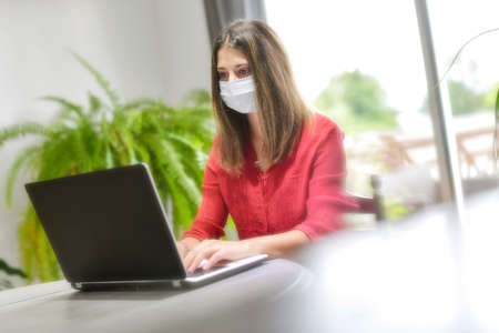 Young female woman wearing a protective mask while she is working at home and attending at a meeting on her computer during the lockdown