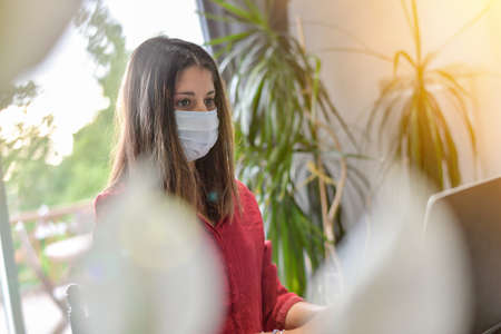 Young woman secretary wearing a protective mask while she is working at home and attending at a meeting on her computer