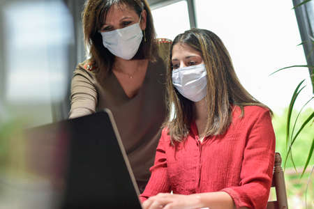 Mother and daughter wearing protective mask and attending online video learning lesson during lockdown