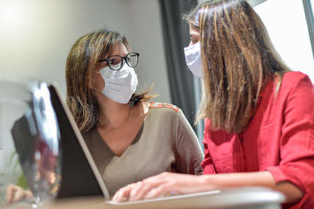 Student and her teacher wearing protective mask and working a lesson on a laptop at home during lockdown Reklamní fotografie