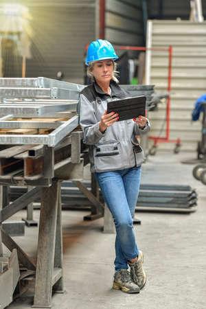 Female worker reading instructions on a digital tablet in the workshop of the company Reklamní fotografie