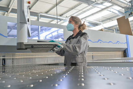 Female engineer is operating on a digital pannel in the company and wearing protections against coronavirus Reklamní fotografie