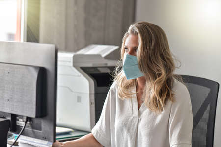 Executive woman working at her desk and wearing a protective mask