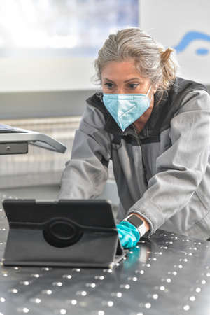 Concentrated female engineer reading her digital tablet in the workshop and wearing a protective mask
