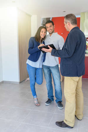 Young couple visits a new flat with a real estate agent