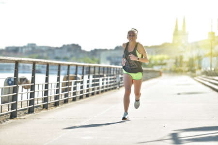 Athlectic woman during her running cession along the river in the city