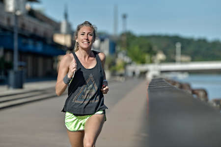 Athletic, middle age female during her running cession along the river
