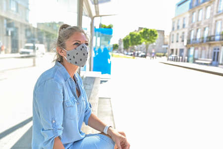 Woman waiting for her tram sitting on a bench and wearing a protective mask