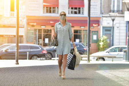 Attractive middle age urban woman walking in the street and carrying bags for shopping while she is wearing a protective mask against  virus. Reklamní fotografie