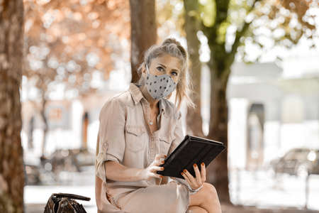 Woman doing a break outdoors during the shutdown, reading on her digital tablet while she is wearing a protective mask against