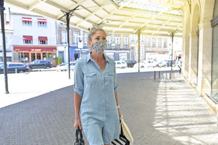 Urban woman doing shopping while she is wearing a protective mask in the street