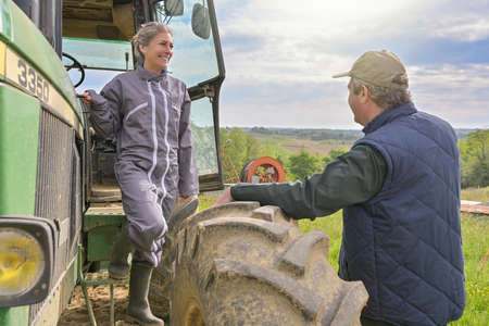 Woman farmer listening the instruction from her boss before to leave the farm with her tractor Reklamní fotografie