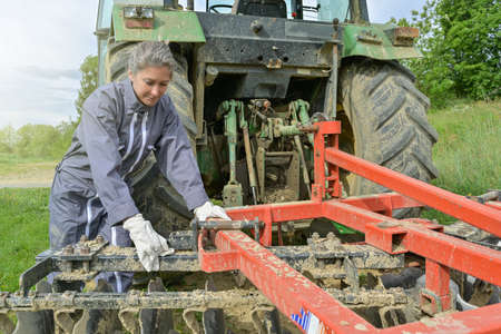 Female farmer adjusting the plow behing the tractor Reklamní fotografie