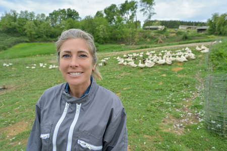 Portrait of a woman standing in the middle of her duck farm in a field