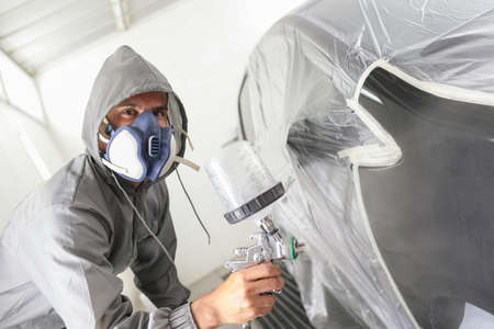 Car body worker paints a car in the paint booth with a spraying paint and a protective mask