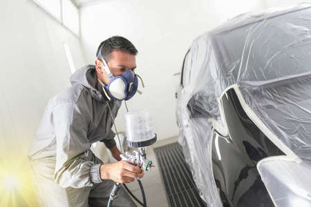 Car body worker paints a car in the paint booth with a spraying paint