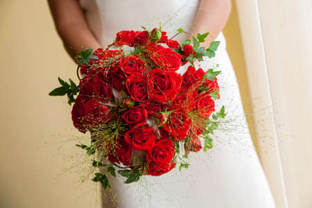Close-up of bride holding red  roses bouquet photo