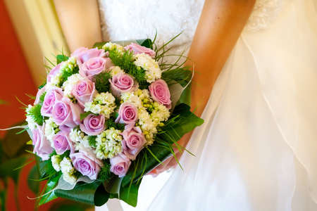 Close-up of bride holding red  roses bouquet