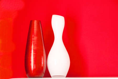 white vase and red vase on white console photo