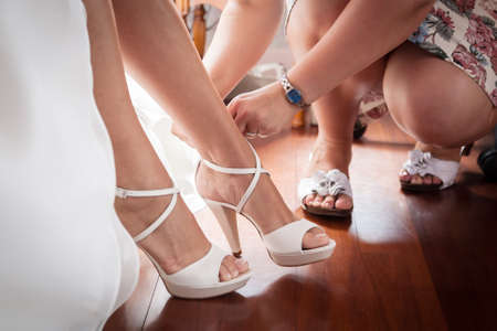 bridesmaid helping to wear  bride the shoes before start of wedding ceremony photo