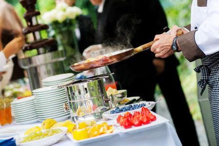outdoor event: Catering event chef is cooking fruit Stock Photo