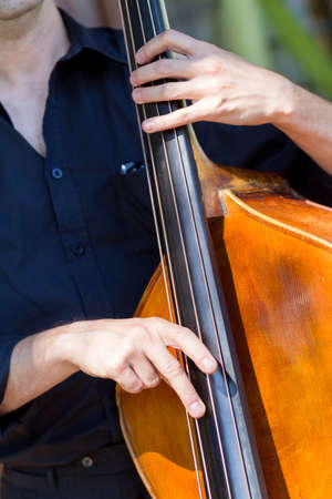 Detail view of a man playing double bass  Imagens