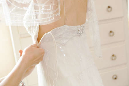 Hands of girls help to the bride to button wedding dress photo