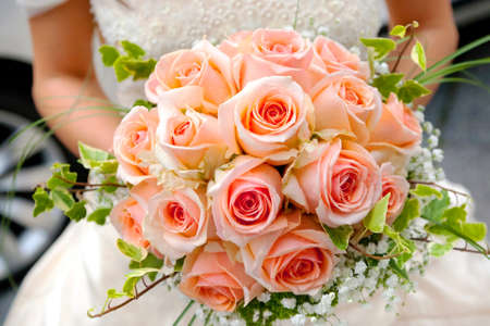 Close-up of bride holding pink roses bouquet photo