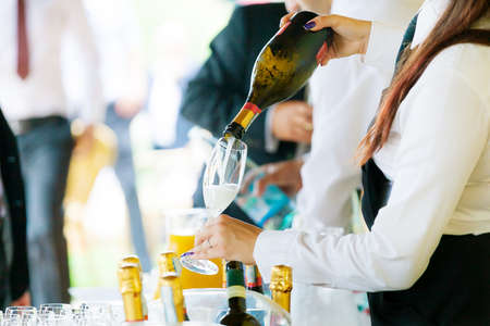 Waiter pouring champagne on a party photo