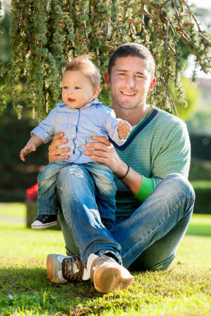 father with baby playing on the park photo