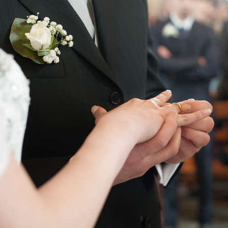 The groom puts  the  wedding ring to finger of the bride photo