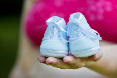 Pregnant woman holding pair of blue shoes for baby boy photo