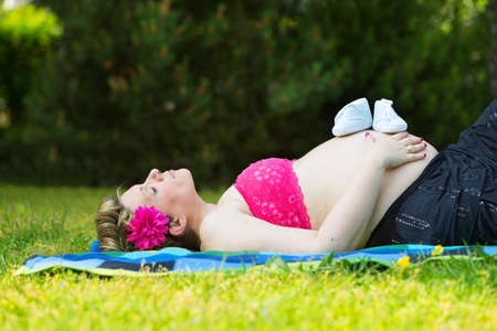 Pregnant woman lying in green grass with baby shoes photo