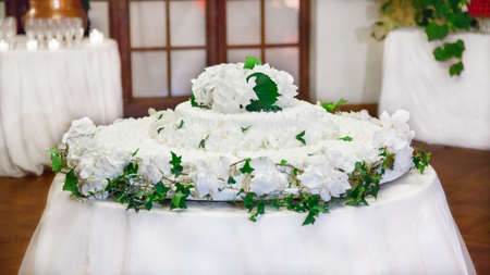 White wedding cake with real flowers decorations photo