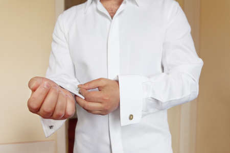 groom wears white shirt and cufflinks photo