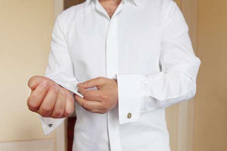 cufflinks: groom wears white shirt and cufflinks Stock Photo