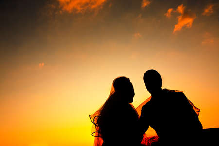 wedding beach: silhouette of a young bride and groom on Sunset background Stock Photo