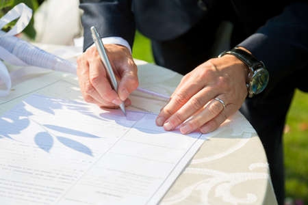 wedlock: groom write on registration of marriage Stock Photo