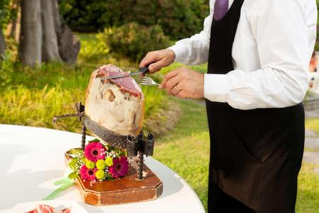 raw ham: Chef slices raw ham.