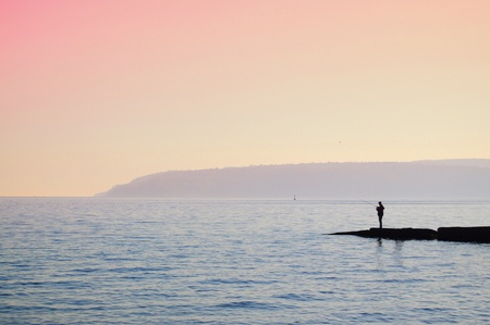 Silhouette of a fisherman at the sea at sunset