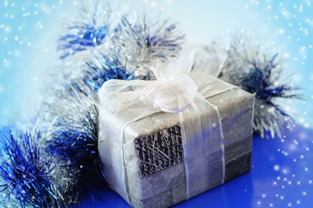 Christmas present in silver wrapping with blue decorations Stock Photo
