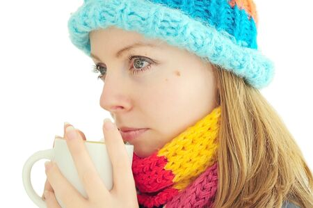 Young woman in hat and scarf enjoying a cup of tea photo