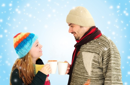 Young couple enjoying a cup of teacoffee with winter background photo